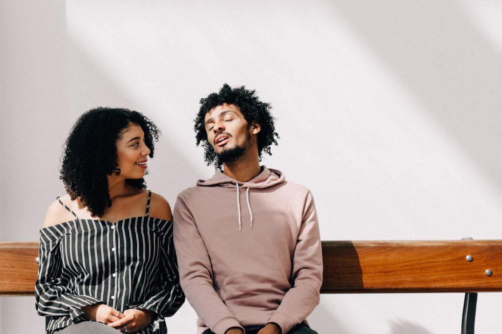man in brown drawstring pullover hoodie sitting on brown bench beside woman